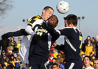 Casey Townsend #11 of the University Michigan heads over Latif Alashe #21 and Chase Tennant #7 during an NCAA quarter-final match against the University of Maryland at Ludwig Field, University of Maryland, College Park, Maryland on December 4 2010.Michigan won 3-2 AET.