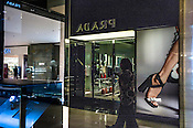 The reflection of a shopper is seen while she walks past the Prada store at the Pavilion, a high end shopping mall in Kuala Lumpur, Malaysia.