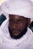 Akadaney, Niger.  Fulani Man.  His aquiline nose suggests Tuareg or Arab ancestry. He wears a headwrap similar to the Tuareg tagelmust.  This is an example of how one culture, the Fulani, in close contact with another, may adopt the other's clothing styles.