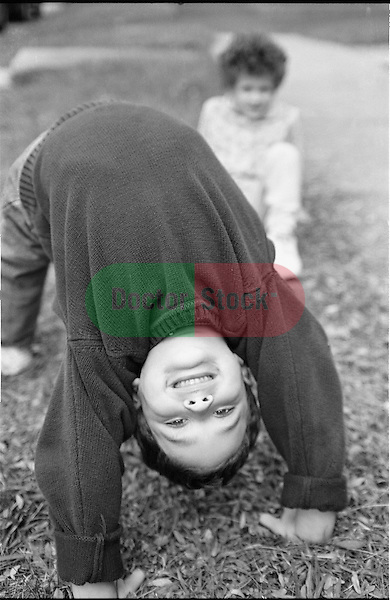 boy (7 years) doing a backbend with girl (5 years) in background
