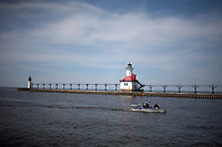 A fishing boat passes a lighthouse as it makes it way up the St. Joseph River from Lake Michigan on Saturday, April 19, 2014, in St. Joseph, Mich. (Photo by James Brosher)