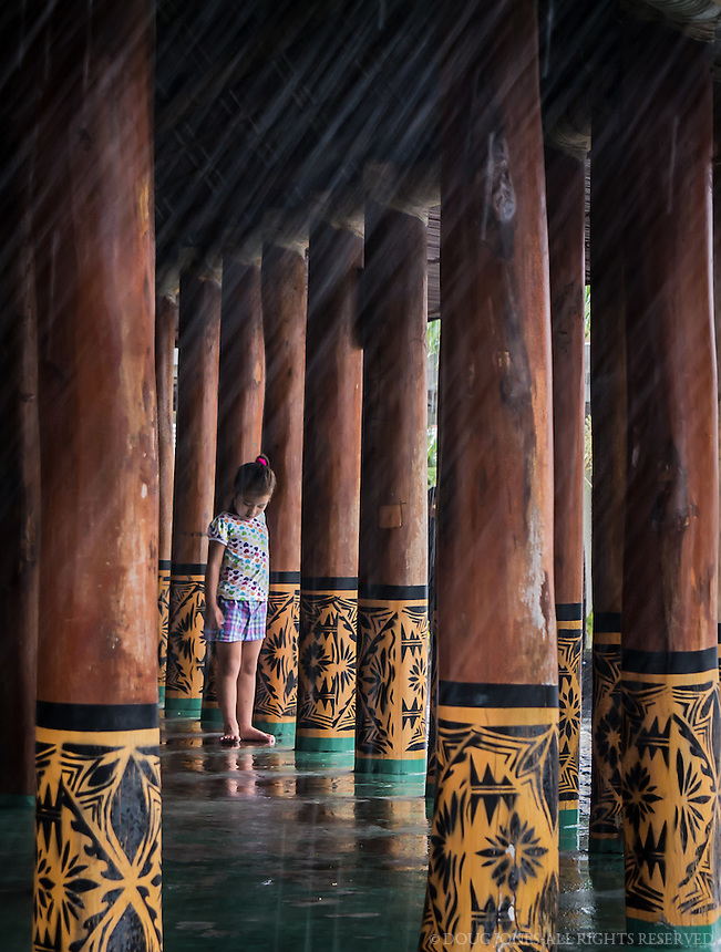 """My wife and I were waiting for an inter-island flight from Pago Pago, in American Samoa, to Apia, in Western Samoa.  Our flight was delayed over an hour due to a major rainstorm affecting both islands.  Totally bored, I kept watching this young Samoan girl playing with her siblings in this large, open structure, supported by this individually carved posts.  I finally grabbed my camera and started photographing the posts and the reflection of the water on the green, painted floor.  After 4-5 shots, the girl ran into the frame, put her hands to her side, and stopped in her tracks as if to gesture, """"Just a moment..."""""""