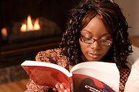 African female student read a book by the fireplace   <br /> photo : (c) images Distribution