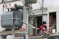 QS040617Shanghai003 20040617 SHANGHAI, CHINA: A worker installs an airconditioner near a electricity transformer in Shanghai, China 17 June 2004. Facing possibly another scorching summer, China may have a gap of 30 million kilowatts between electricity demand and supply this summer. The government has recently announced a price hike in industrial-use electricity to discourage blind and unauthorized expansions in some power-hungry industrial sectors