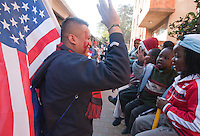 USA fan Adonois Fuentes of New Jersey high-fives  a child outside their apartment building while walking to Ellis Park Stadium for the  2010 World Cup match between the USA and Slovenia in Johannesburg, South Africa on Friday, June 18, 2010.  The USA tied Slovenia 2-2.