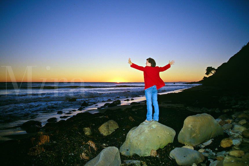 Young woman stands in the wind on the shore of the Pacific Ocean as the sun sets near Malibu, Los Angeles County, California.