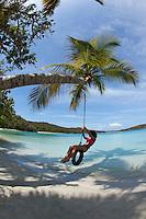 Young woman on a tire swing at  Gibney / Oppenheimer Beach.Virgin Islands National Park.St. John, U.S. Virgin Islands