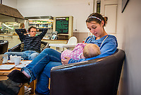 """A mother breastfeeding her baby of eight months in a cafe at a visitor farm park while her husband watches .<br /> <br /> Image from the breastfeeding collection of the """"We Do It In Public"""" documentary photography picture library project: <br />  www.breastfeedinginpublic.co.uk<br /> <br /> <br /> Gloucestershire, England, UK<br /> 30/09/2013<br /> <br /> © Paul Carter / wdiip.co.uk"""