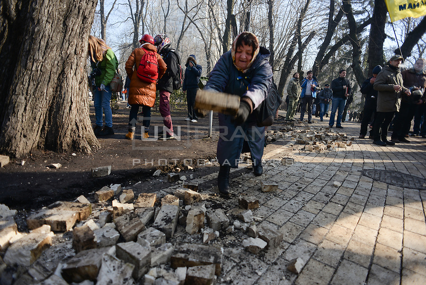 A woman protester help to harvest the paving stones, vastly used during the protest as weapons . Kiev, Ukraine