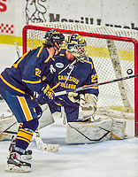 29 December 2013:  Canisius College Golden Griffins goaltender Adam Harris, a Sophomore from Penticton, British Columbia, watches the puck drift dangerously by in the third period against the University of Vermont Catamounts at Gutterson Fieldhouse in Burlington, Vermont. The Catamounts defeated the Golden Griffins 6-2 in the 2013 Sheraton/TD Bank Catamount Cup NCAA Hockey Tournament. Mandatory Credit: Ed Wolfstein Photo *** RAW (NEF) Image File Available ***
