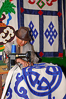 Sewing Tibetan wall hangings, traditional decorations in most Tibetan homes, in the Barkhor, Lhasa, Tibet.  The Eternal Knot and Treasure Vase shown here, two of the Eight Auspicious Symbols in Buddhist culture, represent  infinite wisdom and prosperity.