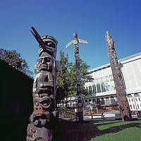 Victoria, BC, Vancouver Island, British Columbia, Canada - Totem Poles in Thunderbird Park beside Royal BC Museum.  Kwakwaka'wakw (Kwakiutl) Totem (carver Mungo Martin) in foreground, Haida Totem (carver Mungo Martin) in right background