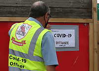 A Ramsgate steward puts a Covid-19 sign on the entrance to the ground during Ramsgate vs Folkestone Invicta, Friendly Match Football at Southwood Stadium on 1st August 2020