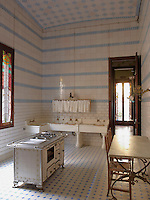 The original kitchen has simpler decoration, with walls lined with white ceramic tiles interspersed with a contrasting row of pale blue tiles and a chequered tiled floor