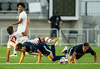 WASHINGTON, DC - SEPTEMBER 6: Maryland defender Brett St. Martin (12) upended by Virginia midfielder Michael Tsicoulias (22) and forward Daniel Wright (23) during a game between University of Virginia and University of Maryland at Audi Field on September 6, 2021 in Washington, DC.