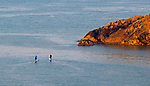 Langland Bay, Swansea, UK, 26th April 2020.<br />The early morning sunlight falls on Snaple Point at Langland Bay near Swansea as a pair of stand up paddleboarders head out to sea in the sunny weather today.