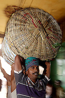 Men carrying large baskets of food and good on their heads in the Kolay market in central Kolkata.<br />