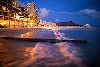 Just after sunset, distant couples stroll in front of hotels while waves wash up along Waikiki Beach, with Diamond Head in the distance, O'ahu.