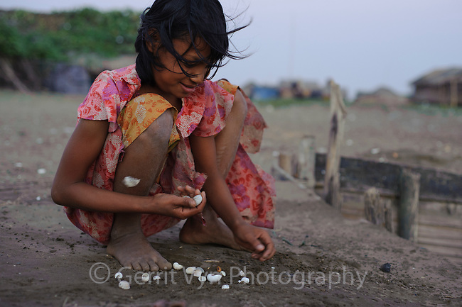 Rakhine girl playing a shell game on Nan Tahr Island, Myanmar.