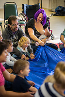 """Breastfeeding a newly arrived baby at a singing and signing group whilst participating in a parachute game.  The woman's husband and older toddler play the game too sitting beside her.Image from the breastfeeding collection of the """"We Do It In Public"""" documentary photography picture library project: <br />  www.breastfeedinginpublic.co.uk<br /> <br /> <br /> Berkshire, England, UK<br /> 27/09/2013<br /> <br /> © Paul Carter / wdiip.co.uk"""
