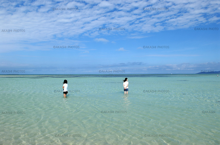 A couple of girls contemplating the beauty of  white sand beach with turquoise waters in Taketomi. Taketomi island, Yaeyama Shoto. Okinawa.