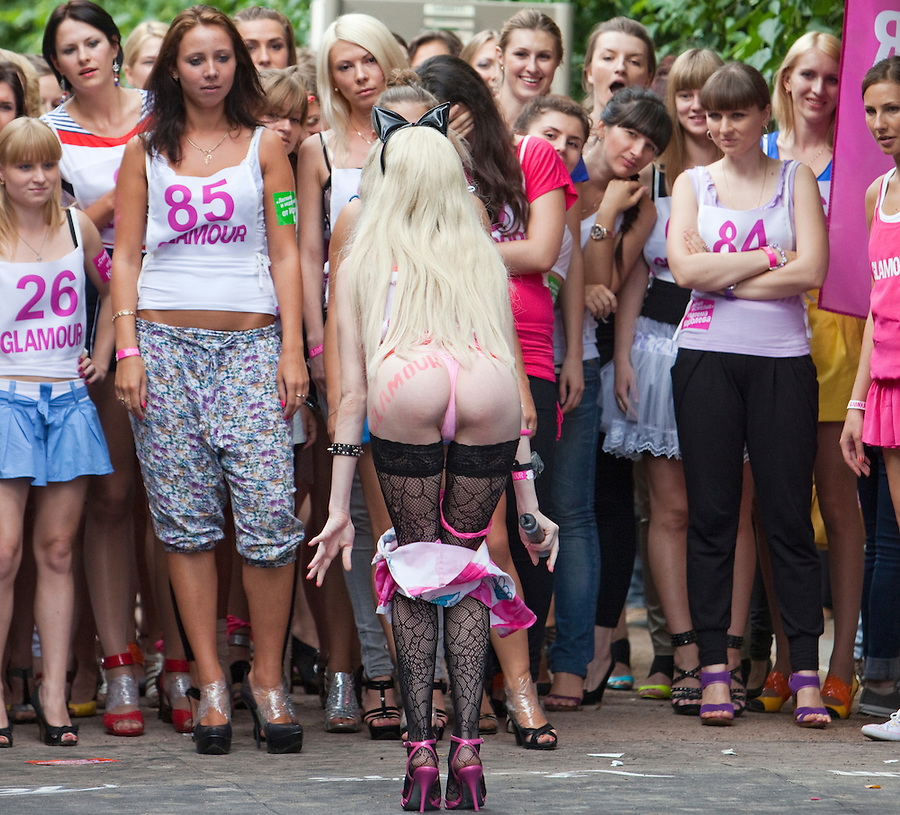 Moscow Russia, 09/07/2011..A woman strips before taking part in a High Heel Race competition organised by Russian Glamour magazine in central Moscow. About 100 young women took part in a series of races.