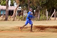 A Kenyan schoolboy runs to school on a dirt road in Iten, Kenya.