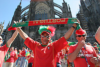 Portugese Fans cheer and dance while carrying and beating drums outside the Kölner Dom cathedral  in Cologne, Germany.  The fans were getting ready for the Portugal national soccer team's first round FIFA World Cup match against Angola in Cologne, Germany on Sunday, June 11th 2006.