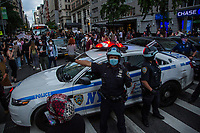 NEW YORK, NEW YORK - JUNE 1: View of a police car with two police officers in the midst of protesters on June 1, 2020 in New York. The protests spread across the country in at least 30 cities across the United States, over the death of unarmed black man George Floyd at the hands of a police officer, this is the latest death in a series of police deaths of black Americans. Today is the first night of a curfew in New York City (Photo by Pablo Monsalve / VIEWpress via Getty Images)