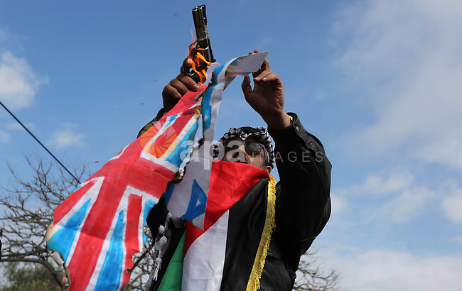 A Palestinian demonstrator gestures as he holds representations of Israeli, British and U.S. flags before burning them during a protest against a U.S. decision to cut aid, in Gaza City January 29, 2018. Photo by Ashraf Amra