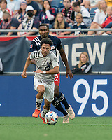 FOXBOROUGH, MA - JULY 25: Joaquin Torres #18 of CF Montreal dribbles as Jon Bell #23 of New England Revolution defends during a game between CF Montreal and New England Revolution at Gillette Stadium on July 25, 2021 in Foxborough, Massachusetts.