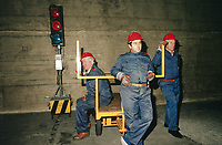 Switzerland. Canton Lucerne. Three bored men with red helmets and a mobile traffic light in the Sonnenberg tunnel in Lucerne during the largest civil defense exercise ever held in the country. From 16 to 21 November 1987, almost 1200 men and women converted a motorway tunnel into perhaps the world's largest bunker structure. The civil protectors had to prove during the exercise «Ameise » ( Ants in english) that in an emergency more than 20,000 inhabitants of the city of Lucerne could survive here in the mountain for two weeks. The Sonnenberg Tunnel is a 1,550 m  long motorway tunnel, constructed between 1971 and 1976. At its completion it was also the world's largest civilian nuclear fallout shelter, designed to protect 20,000 civilians in the eventuality of war or disaster. Based on a federal law from 1963, Switzerland aims to provide nuclear fallout shelters for the entire population of the country. The construction of a new tunnel near an urban centre was seen as an opportunity to provide shelter space for a large number of people at the same time. The giant bunker was built between 1970 and 1976 at a cost of 40 million Swiss francs. The shelter consisted of the two motorway tunnels (one per direction of travel), each capable of holding 10,000 people in 64 person subdivisions. A seven story cavern between the tunnels contained shelter infrastructure including a command post, an emergency hospital, a radio studio, a telephone centre, prison cells and ventilation machines. The shelter was designed to withstand the blast from a 1 megaton nuclear explosion 1 kilometer away. The blast doors at the tunnel portals are 1.5 meters thick and weigh 350 tons. The logistical problems of maintaining a population of 20,000 in close confines were not thoroughly explored, and testing the installation was difficult because it required closing the motorway and rerouting the usual traffic. The only large-scale test, a five-day exercise in 1987 to practice converting the road tun