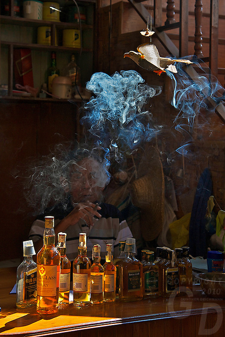Shop keeper and local whisky during Inle Lake Festival - Inle Lake, Shan State, Myanmar