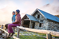 The Via Alta Verzasca is a five day ridge traverse hike above the Valle Verzasca in the Ticino region of Switzerland. At the Capanna Borgna, the first hut on the route, two women watch the sunset.