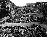 Rows of bodies of dead inmates fill the yard of Lager Nordhausen, a Gestapo concentration camp.  This photo shows less than half of the bodies of the several hundred inmates who died of starvation or were shot by Gestapo men.  Germany, April 12, 1945.  Myers.  (Army)<br /> NARA FILE #:  111-SC-203456<br /> WAR & CONFLICT BOOK #:  1121
