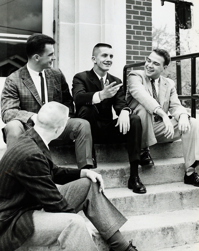 Four young men sitting on outdoor stairs. 1950's.