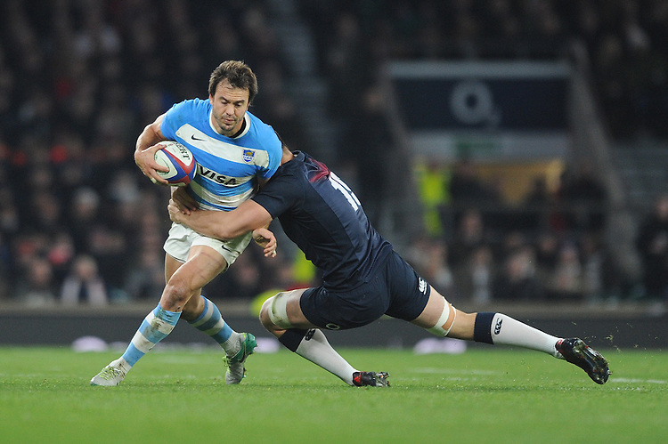 Juan Martín Hernández of Argentina is tackled by Charlie Ewels of England during the Old Mutual Wealth Series match between England and Argentina at Twickenham Stadium on Saturday 26th November 2016 (Photo by Rob Munro)