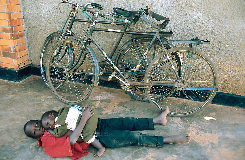 Uganda. Kayunga district. Kayunga. Youth centre.  Two brothers lay on the concrete ground. The oldest boy holds the youngest child in his arms and on his stomach. © 2004 Didier Ruef