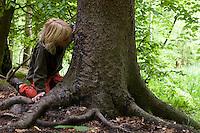 Kind riecht an einem Schubberbaum, Kratzbaum, Malbaum, Wildschwein hat durch Reiben die Rinde im unteren Bereich eines Baumes abgewetzt, Schwarzwild, Sus scrofa, wild boar, pig