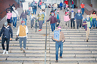 Protestors walk down stairs near Boston City Hall as they make their way to Faneuil Hall during the 2020 Women's March protest in opposition to the re-election of US president Donald Trump in Boston, Massachusetts, on Sat., Oct. 17, 2020.