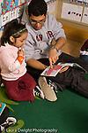 Preschool New York City ages 4-5 high school male volunteer reading book to girl vertical