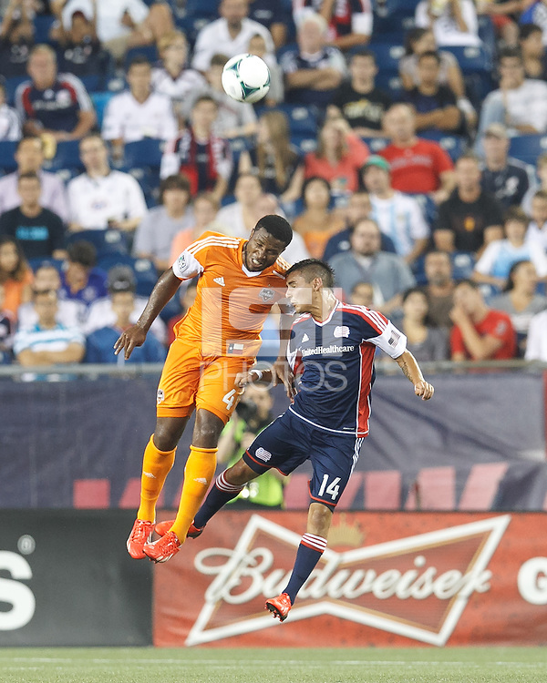 Houston Dynamo defender Jermaine Taylor (4) and New England Revolution midfielder Diego Fagundez (14) battle for head ball.  In a Major League Soccer (MLS) match, Houston Dynamo (orange) defeated the New England Revolution (blue), 2-1, at Gillette Stadium on July 13, 2013.