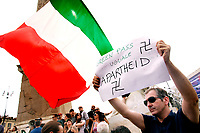 A man shows a banner 'Green pass is like Apartheid' during the demonstration against the green pass, that certifies the vaccination against covid 19, after the last decree of the council of ministers, necessary to enter public places, such as offices, schools but also restaurants..<br /> Rome (Italy), July 27th 2021<br /> Photo Samantha Zucchi Insidefoto