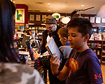 """July 26, 2017. Raleigh, North Carolina.<br />  <br /> Alan Gratz signs a book for early arriver Collin Aherne, age 12, who was also vlogging the encounter on his phone. <br /> <br /> Author Alan Gratz spoke about and signed his new book """"Refugee"""" at Quail Ridge Books. The young adult fiction novel contrasts the stories of three refugees from different time periods, a Jewish boy in 1930's Germany , a Cuban girl in 1994 and a Syrian boy in 2015."""