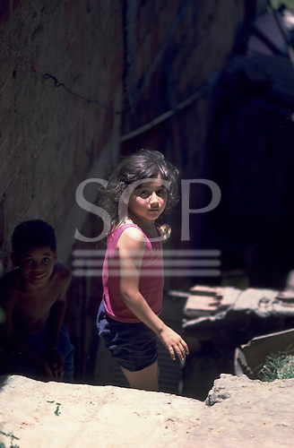 Rio de Janeiro, Brazil; girl in sunlight looking apprehensive with a smiling boy in the shadows.