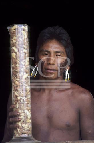 A-Ukre village, Xingu, Brazil. Kayapo man holding a measuring cylinder full of Brazil nuts for the Body Shop; Para State.