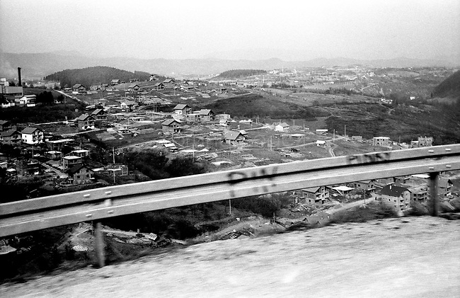 BOSNIA-HERZEGOVINA, Belgrade-Sarajevo Road, 03/2003..Lanscape pictures taken from the bus between Belgrad and Sarajevo. .View on Vlasenica. In Vlasenica, the bus chooses to do not enter in the croato-muslim federation and runs by the road on the west-south in direction of Sokolac..BOSNIE-HERZEGONVINE, Route Belgrade-Sarajevo, 03/2003..Photo prise depuis le bus qui relie Belgrade à Sarajevo. Vue de Vlasenica. A cet endroit, le chauffeur du bus choisit de ne pas entrer dans la fédération croato-musulmane et prend la direction du sud-ouest vers Sokolac..  © Bruno Cogez