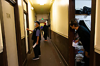 A resident in the Bing Kung building, a single room occupancy building, peers out from his door at the commotion in the hallway on April 21, 2020 in the Chinatown-International District in Seattle, WA. Rachtha Danh, from the Seattle Chinatown International District Preservation and Development Authority (SCIDpda) is delivering masks to residents with the help from the building manager. Each bag contains 3 masks that were handmade and donated. (Photo by Karen Ducey)