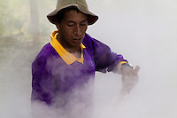 A Colombian peasant works in the smoke of boiling sugar cane juice during the processing of panela in a rural sugar cane mill (trapiche) in San Agustín, Colombia, 18 April 2004. Panela, a solid block of raw, unrefined sugar, is made by cooking and evaporation of the sugar cane juice into a golden, sticky syrup which is then poured into the wooden molds and allowed to solidify. Having the taste like a cross between molasses and brown sugar, panela is served as a hot or cold infusion (aguapanela). Due to the large amounts of proteins, vitamins and minerals and thus, panela is believed to have healing powers. Cheaper than sugar, it is consumed by the majority of Colombians and it is a major source of calories for children from families with low socioeconomic status. With more than 70,000 farms that cultivate sugarcane for mills, panela production is an important economic activity in the Colombian countryside, employing around 350,000 people and being the second largest source of jobs after agricultural coffee production.