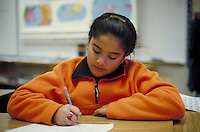 STUDENT WRITING AT HER DESK. ELEMENTARY SCHOOL STUDENTS. OAKLAND CALIFORNIA USA CARL MUNCK ELEMENTARY SCHOOL.
